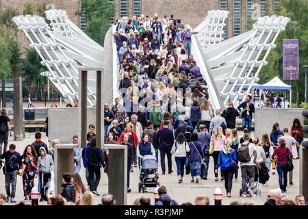 London London England Great Britain United Kingdom Millennium Bridge steel suspension footbridge pedestrian crossing Thames River crowded multi-ethnic - Stock Photo