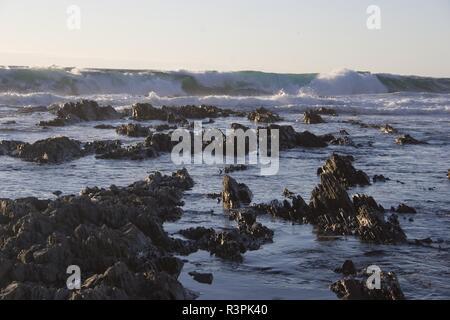 waves crashing onto a rocky shore - Stock Photo