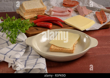 Ingredients preparations of traditional Portuguese snack food. Francesinha sandwich of bread, cheese, pork, ham, sausages. On table. - Stock Photo