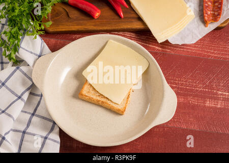 Ingredientes preparations of traditional Portuguese snack food. Francesinha sandwich of bread, cheese, pork, ham, sausages. On table. - Stock Photo