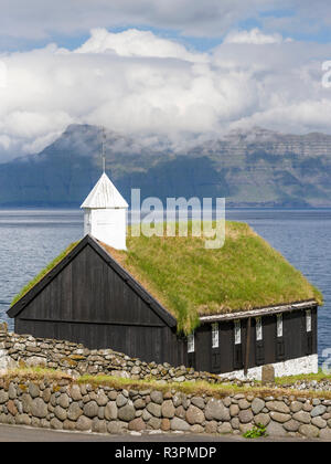 Church of Funningur, in the background Funningsfjordur, Leiriksfjordur and the island Kalsoy. Northern Europe, Denmark - Stock Photo