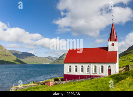 The church in village Husar on Kalsoy, in the background the island of Bordoy and Klaksvik. Faroe Islands, Denmark - Stock Photo