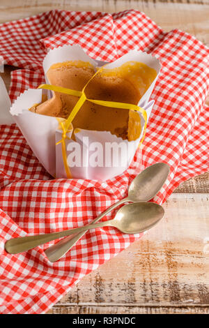 Portuguese sponge cake wrapped in the typical paper used on the baking, on wooden background. - Stock Photo