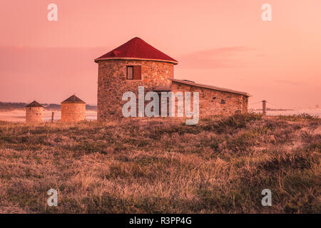 Old traditional wind-mills in sand-hills of Apulia Portugal. - Stock Photo