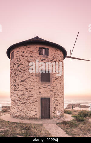 Old traditional wind-mill in sand-hills of Apulia Portugal. - Stock Photo