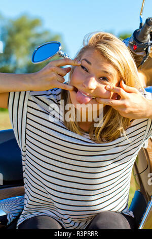 young blond woman making a grimace - Stock Photo