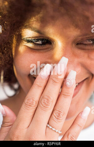 Portrait of laughing young woman with artificial nails