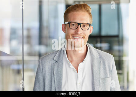 Portrait of smiling redheaded businessman wearing glasses - Stock Photo