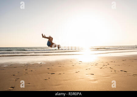 Young man doing somersaults on the beach - Stock Photo