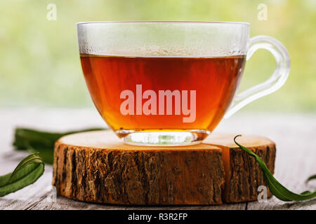Herbal drink Ivan-tea in transparent cup close-up on wooden table - Stock Photo