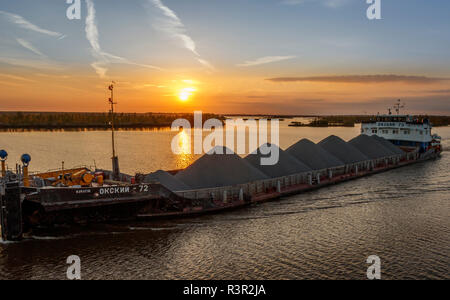 A fully laden barge sailing as the sun sets on Lake Onega in North-West Russia. - Stock Photo