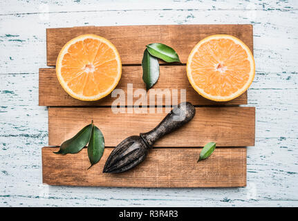 fresh sliced orange with leaves, and a wooden crush for juice, on a wooden tray, on a white rustic background, top view, close up - Stock Photo
