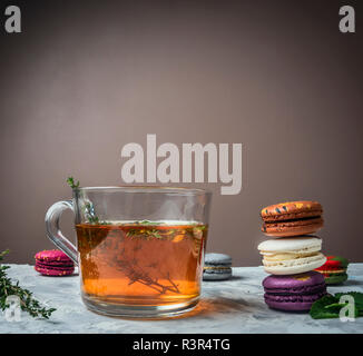 tea with herbs, cumin, mint, appetizing macaroons, on a white table, on a blurry background, space for text - Stock Photo