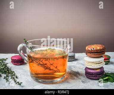 Healthy hot herbal tea with berries, thyme and mint, appetizing, multicolored macaroons, piled on a white rustic background, space for text - Stock Photo
