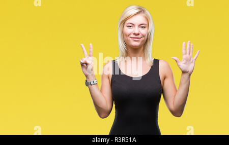 Young beautiful blonde attractive woman wearing elegant dress over isolated background showing and pointing up with fingers number seven while smiling - Stock Photo