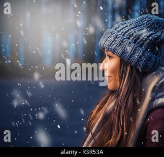 smiling girl in autumn clothes is standing on the street, snow is falling around, blure - Stock Photo