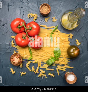different types of pasta, laid out with various ingredients, tomatoes, herbs, oil in a decanter and seasonings on a dark rustic background, healthy ve - Stock Photo