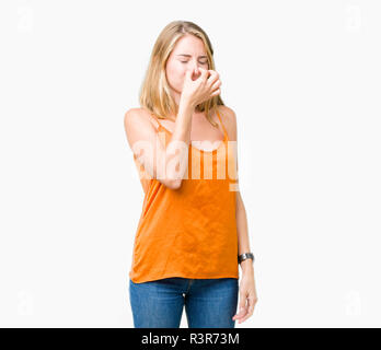 Beautiful young woman wearing orange shirt over isolated background smelling something stinky and disgusting, intolerable smell, holding breath with f - Stock Photo
