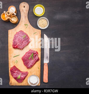 Appetizing raw beef, on a vintage cutting board, with rosemary, meat knife, butter and spices, border, place for text on a rustic wooden background - Stock Photo