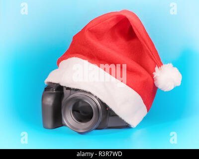 Photo camera under red Christmas hat. On blue - Stock Photo