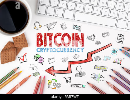 Bitcoin price crash concept with icons. Computer keyboard and cup of coffee on a white table - Stock Photo