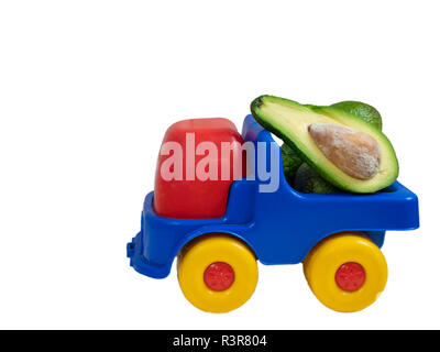 big toy truck with avocado fruit cut in a half. closeup side shot isolated on white background - Stock Photo