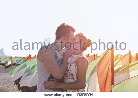 Couple kisses between flags of United Arab Emirates. United Arab Emirates Anniversary Celebration on the kite beach in Dubai. National day - Stock Photo