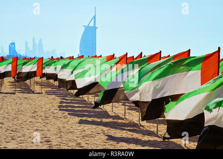 View of hotel in Dubai and lot of flags United Arab Emirates for the anniversary celebration on beach - Stock Photo