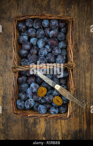 Wicker basket of organic plums, wooden table - Stock Photo