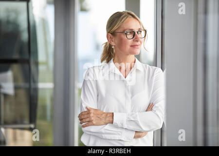 Businesswoman in office leaning against window, with arms crossed - Stock Photo