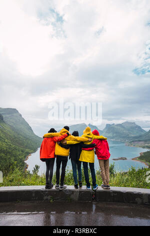 Norway, Senja island, rear view of friends embracing on an observation point at the coast - Stock Photo