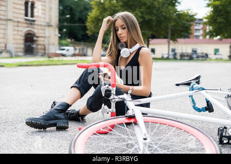 Relaxed teenage girl sitting down using cell phone next to bicycle - Stock Photo