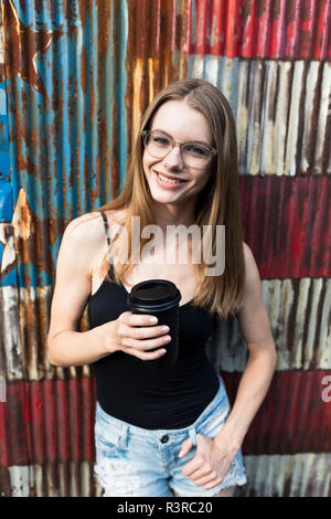 Young woman holding cup of coffee, standing in front of metal fence with stars and stripes - Stock Photo