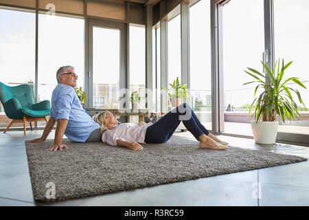 Mature couple relaxing at home looking out of window - Stock Photo