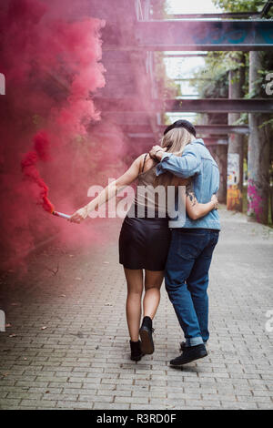 Young couple with smoke torch walking outdoors - Stock Photo