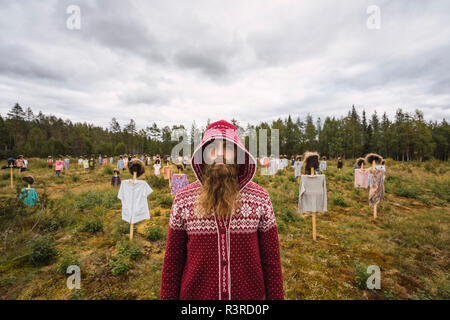 Finland,  Suomussalmi, Man standing in front of The Silent People, art project with crowd of scare crows - Stock Photo