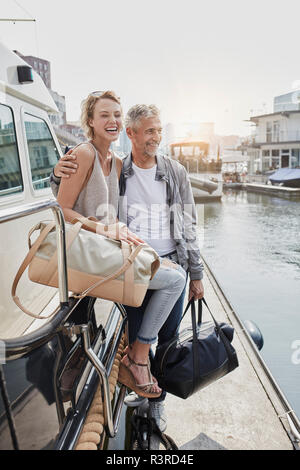 Older man and young woman standing with travelling bags on jetty next to yacht - Stock Photo