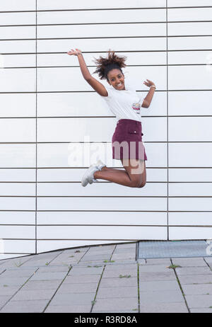 Portrait of laughing young woman jumping in the air - Stock Photo