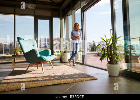 Mature woman standing at the window at home looking out