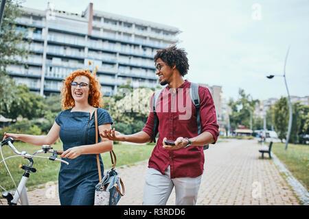 Friends walking in park, talking, woman pushing bicycle - Stock Photo