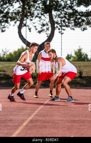 Three young men playing basketball on an outdoor court - Stock Photo