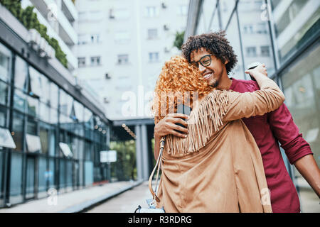 Colleagues meeting in the city, embracing - Stock Photo