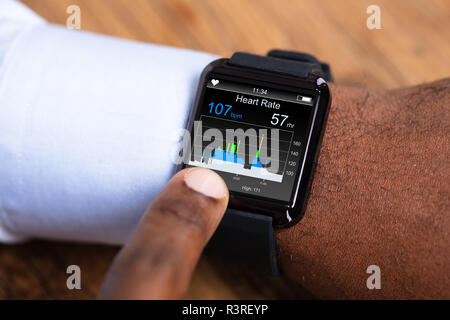 Close-up Of A Man Using Black Smartwatch Showing Heart Rate - Stock Photo
