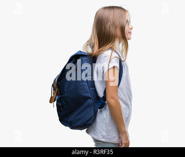 Young beautiful smart student girl wearing backpack over isolated background looking to side, relax profile pose with natural face with confident smil - Stock Photo