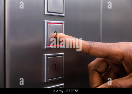 Close-up Of A Man's Finger Pressing On Second Floor Elevator Button - Stock Photo