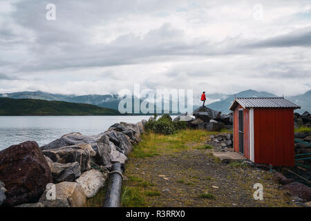 Norway, Senja island, man standing on a rock at the coast - Stock Photo