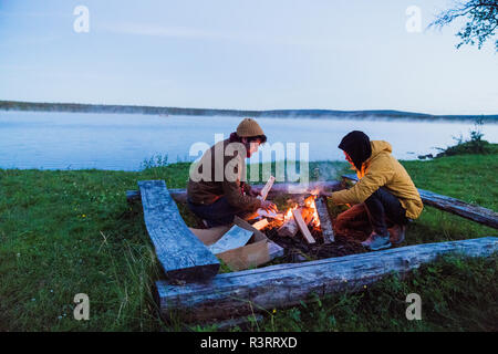 Sweden, Lapland, Two friends preparing a bonfire at the lakeshore - Stock Photo
