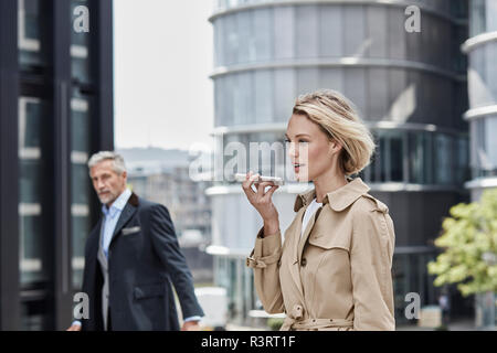 Germany, Duesseldorf, portrait of  blond businesswoman wearing beige trenchcoat talking on mobile phone - Stock Photo