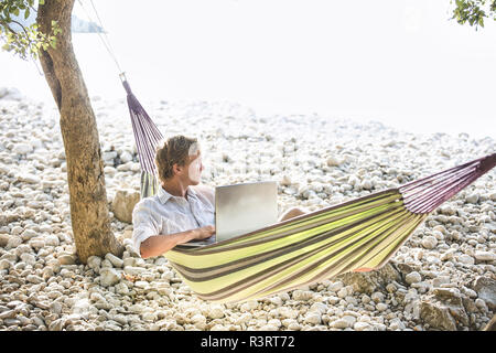 Croatia, Cres Island, man with laptop lying in hammock on a beach looking at distance - Stock Photo