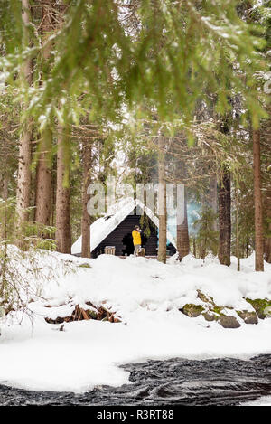 Finland, Kuopio, woman standing in front of wooden hut in winter - Stock Photo